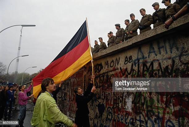 A jubilant man waves the German national flag at a row of East German border guards atop the Berlin Wall soon to be demolished 12th November 1989