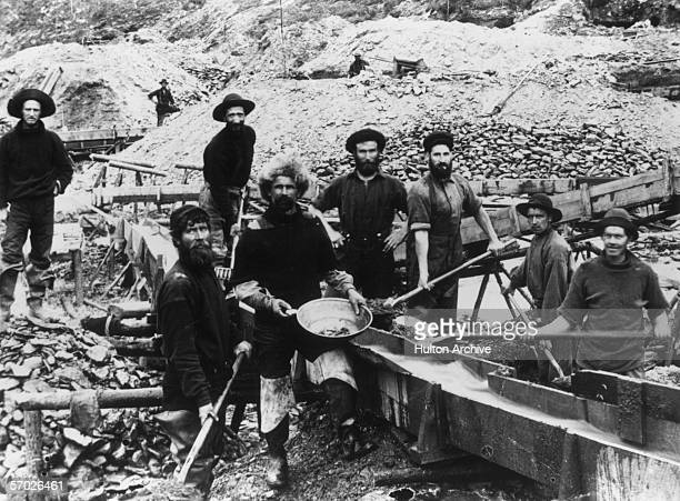 Jubilant miners display a large gold nugget during the Klondike Gold Rush circa 1897