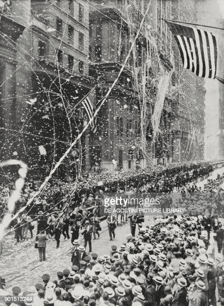 A jubilant parade escorts along Broadway the American aviator Wiley Post and his navigator Harold Charles Gatty back from their 8 days flight around...