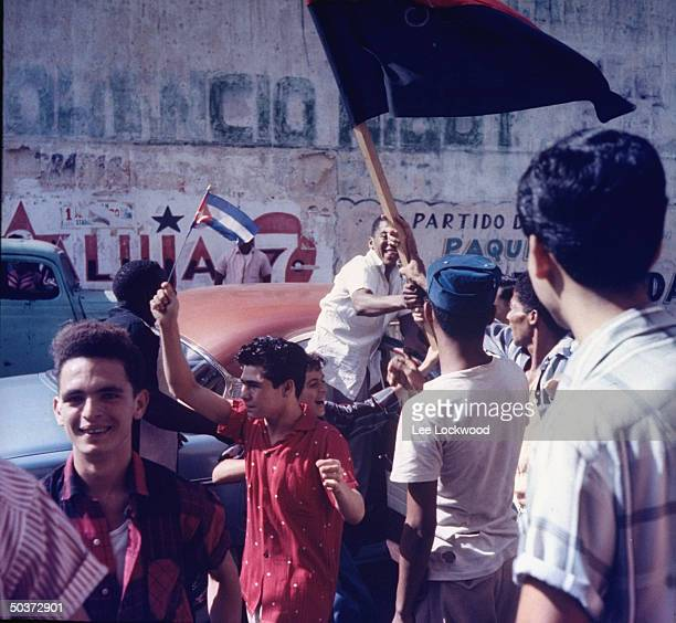 Jubilant population gathering on Havana street w Cuban flags held proudly as victorious Castro and rebel army head toward city