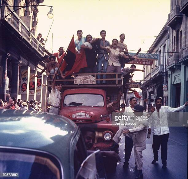 Jubilant population gathering on Havana streets by truck and foot as victorious Castro and rebel army head toward city