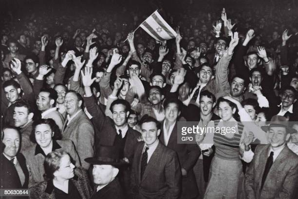 Jubilant residents celebrate with what would become the Israeli flag after the United Nations decision to approve the partition of Palestine November...