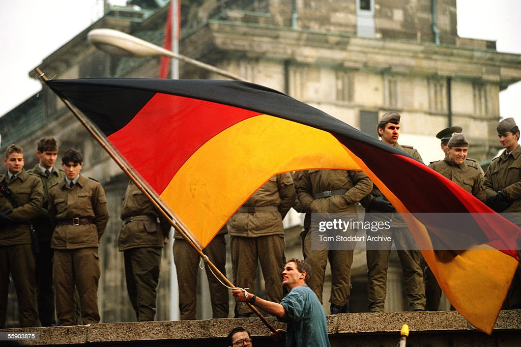 A jublilant man waves the German national flag under the gaze of suspicious East-German border guards on top of the Berlin Wall on the morning of November 10th 1989, the day the wall finally came down.