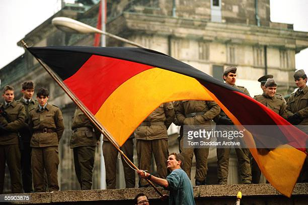 A jublilant man waves the German national flag under the gaze of suspicious EastGerman border guards on top of the Berlin Wall on the morning of...