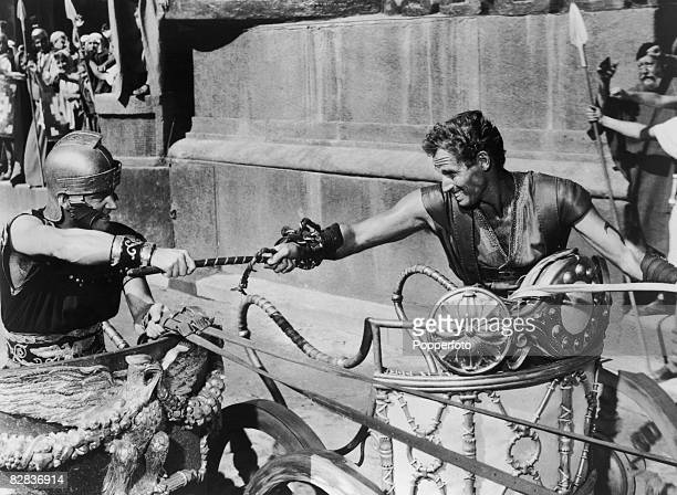 Judah BenHur played by American actor Charlton Heston struggles with Messala played by Stephen Boyd during the chariot race from the film 'Ben Hur'...