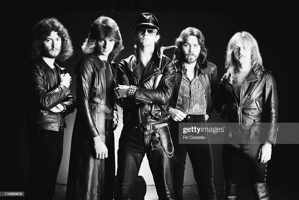 Judas Priest (drummer Les Binks, bassist Ian Hill, singer Rob Halford, guitarist Glenn Tipton and guitarist K. K. Downing), British heavy metal band. pose against a dark background, wearing black leather clothing, in a group studio portrait, circa 1978.