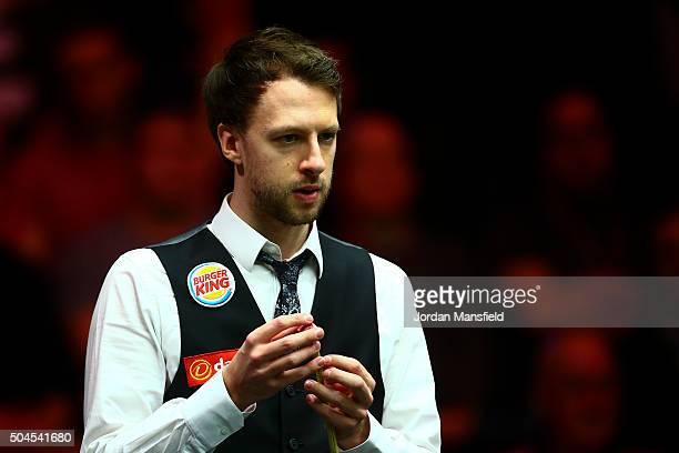 Judd Trump of England chalks his cue in his first round match against Stephen Maguire of Scotland during Day Two of the Dafabet Masters at Alexandra...