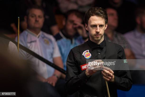 Judd Trump of England chalks the cue against Rory McLeod of England during his first round match on day four of Betfred World Championship 2017 at...