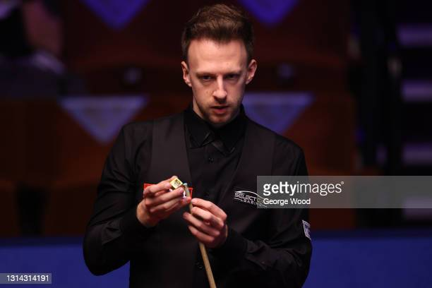 Judd Trump of England chalks the cue during the Betfred World Snooker Championship Round Two match between David Gilbert of England and Judd Trump of...