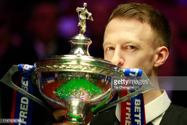 Judd Trump of England kisses his trophy after winning the final match against John Higgins of Scotland on day 17 of the 2019 Betfred World Snooker...