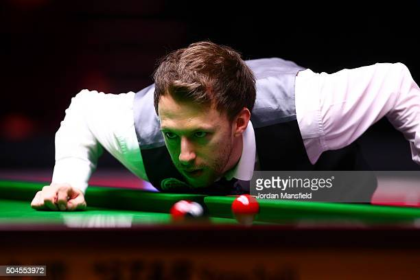 Judd Trump of England lines up a shot in his first round match against Stephen Maguire of Scotland during Day Two of the Dafabet Masters at Alexandra...