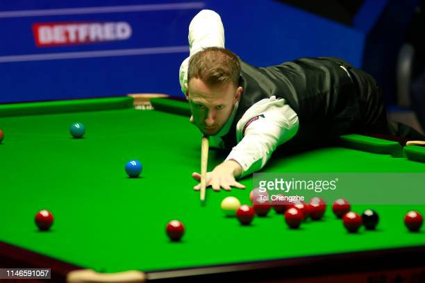 Judd Trump of England plays a shot in the semi-final match against Gary Wilson of England on day thirteen of the 2019 Betfred World Snooker...