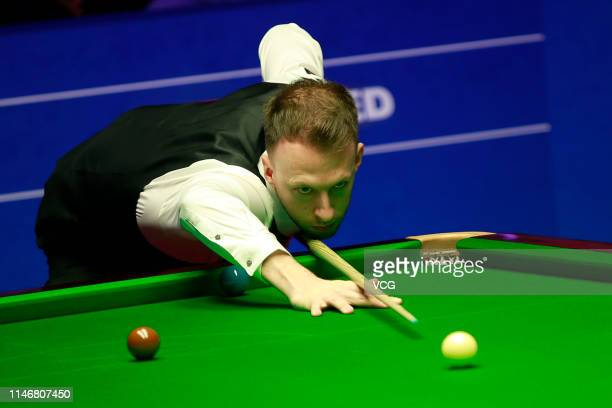 Judd Trump of England plays a shot in the semifinal match against Gary Wilson of England on day fourteen of the 2019 Betfred World Snooker...