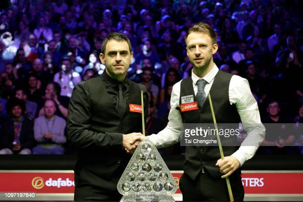 Judd Trump of England shakes hands with Ronnie O'Sullivan of England prior to their final match on day eight of The Dafabet Masters at Alexandra...