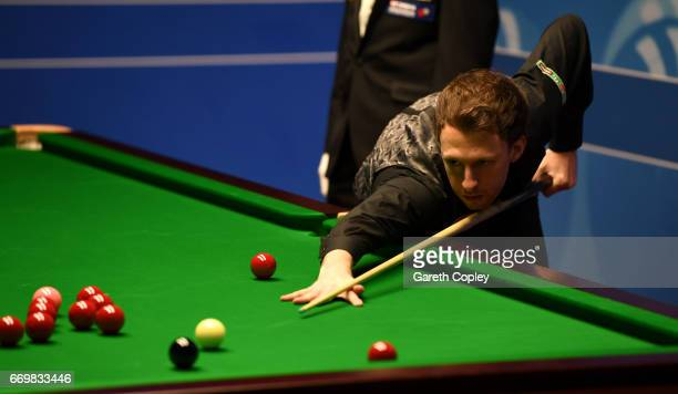 Judd Trump plays a shot against Rory McLeod during their first round match of the World Snooker Championship at Crucible Theatre on April 18 2017 in...