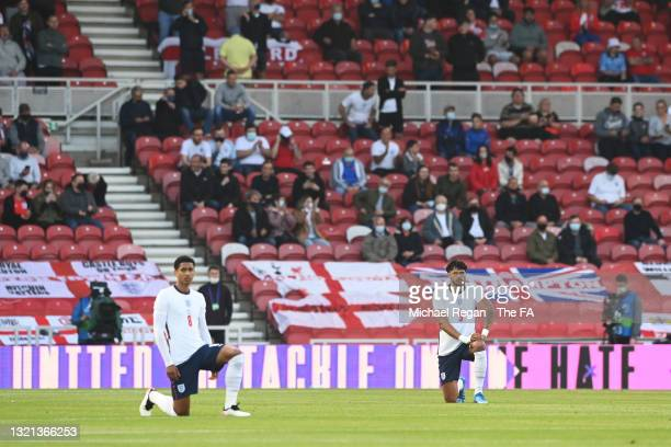 Jude Bellingham and Tyrone Mings of England take the knee ahead of the international friendly match between England and Austria at Riverside Stadium...