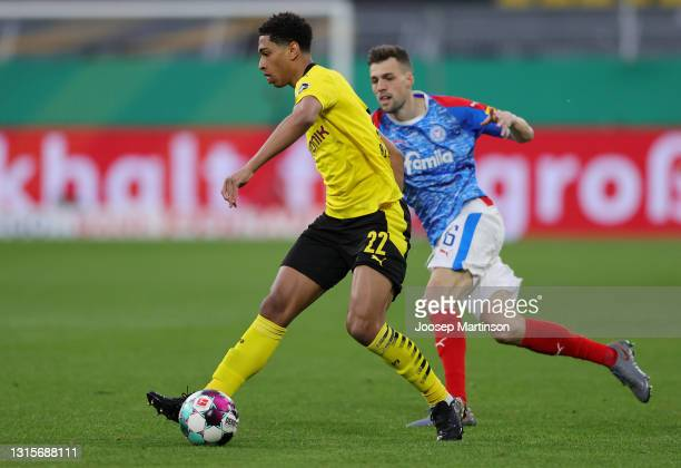 Jude Bellingham of Borussia Dortmund battles for possession with Jonas Meffert of Holstein Kiel during the DFB Cup semi final match between Borussia...