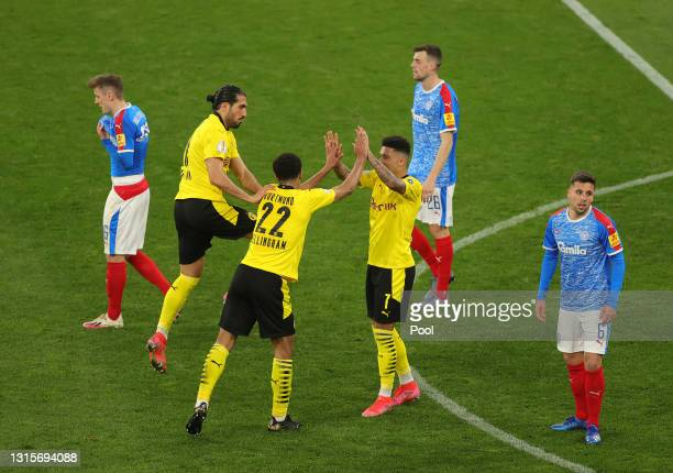 Jude Bellingham of Borussia Dortmund celebrates with Jadon Sancho after scoring their side's fifth goal during the DFB Cup semi final match between...