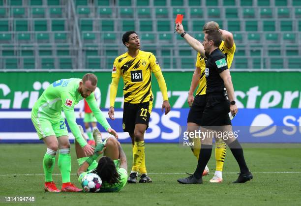 Jude Bellingham of Borussia Dortmund is shown a red card and sent off by referee Tobias Stieler during the Bundesliga match between VfL Wolfsburg and...