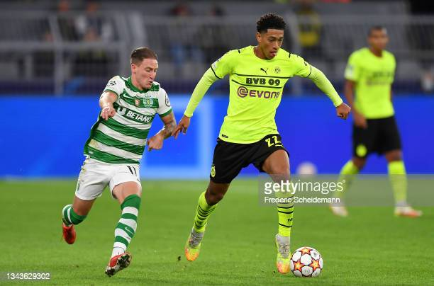 Jude Bellingham of Borussia Dortmund runs with the ball whilst under pressure from Nuno Santos of Sporting CP during the UEFA Champions League group...