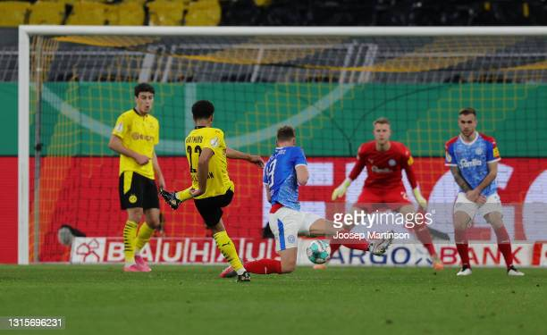 Jude Bellingham of Borussia Dortmund scores their side's fifth goal past Thomas Dahne of Holstein Kiel during the DFB Cup semi final match between...