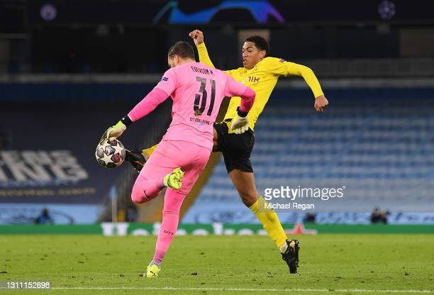 Jude Bellingham of Borussia Dortmund tackles Ederson of Manchester City to win the ball during the UEFA Champions League Quarter Final match between...