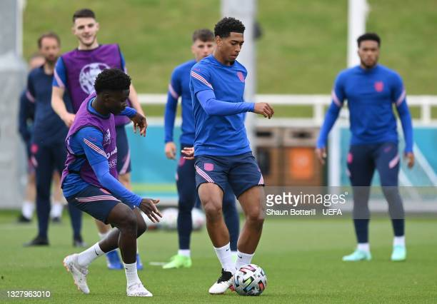 Jude Bellingham of England is challenged by teammate Bukayo Saka during the England Training Session at St George's Park on July 10, 2021 in Burton...