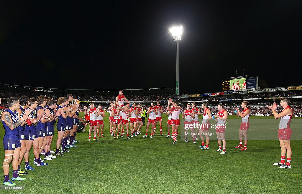 Jude Bolton of the Swans gets carried off by Jarrad Mcveigh (L) and Ryan O'Keefe during the AFL Second Preliminary Final match between the Fremantle Dockers and the Sydney Swans at Patersons Stadium on September 21, 2013 in Perth, Australia.