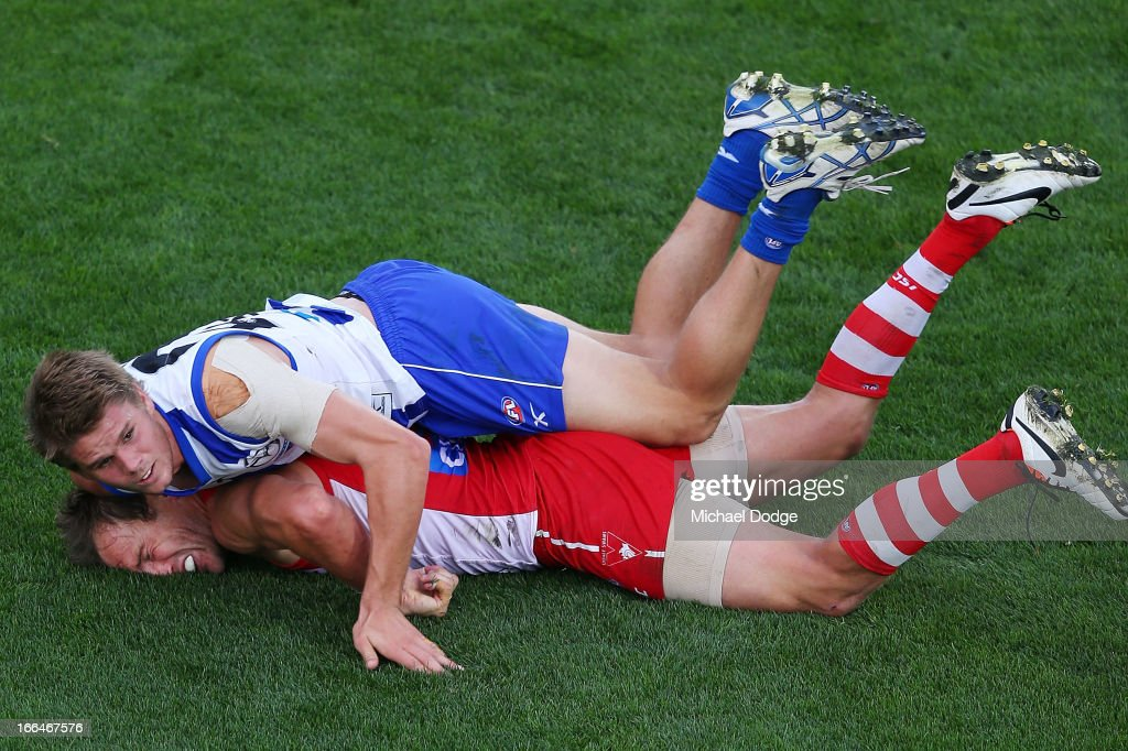 Jude Bolton of the Swans gets crushed in a tackle by Taylor Hine of the Kangaroos during the round three AFL match between the North Melbourne Kangaroos and the Sydney Swans at Blundstone Arena on April 13, 2013 in Hobart, Australia.