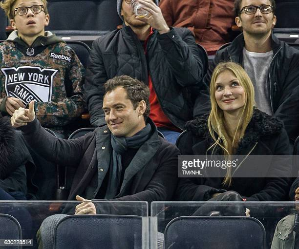 Jude Law and Philipa Coan are seen during New Jersey Devils Vs New York Rangers at Madison Square Garden on December 18 2016 in New York City