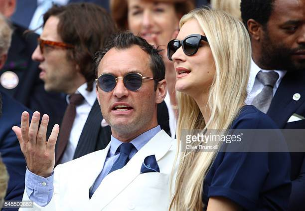 Jude Law and Phillipa Coan watch on as Roger Federer of Switzerland plays Milos Raonic of Canada in the Men's Singles Semi Final match on day eleven...
