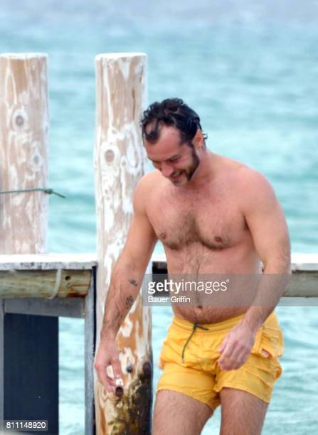 e5a8a2081c Jude Law wears yellow swim trunks as he goes for a swim with a ...