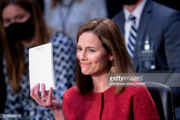 Judge Amy Coney Barrett, holds up a blank notepad after Senator John Cornyn asked her what documents she had on her desk during the second day of her...