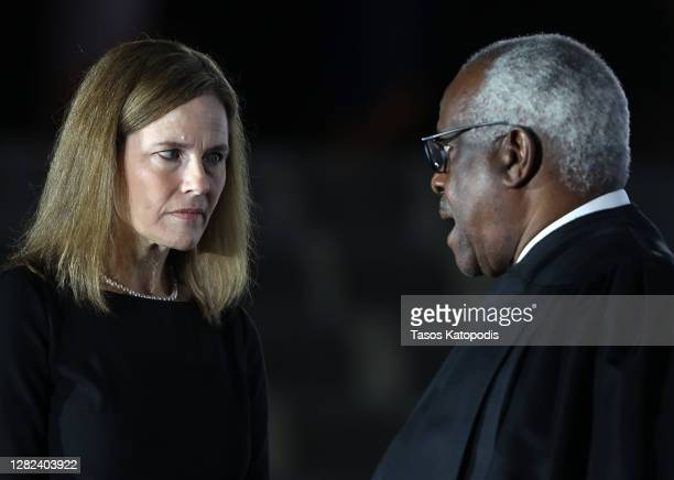 Judge Amy Coney Barrett talks with Supreme Court Associate Justice Clarence Thomas during her ceremonial swearing-in ceremony to be U.S. Supreme...
