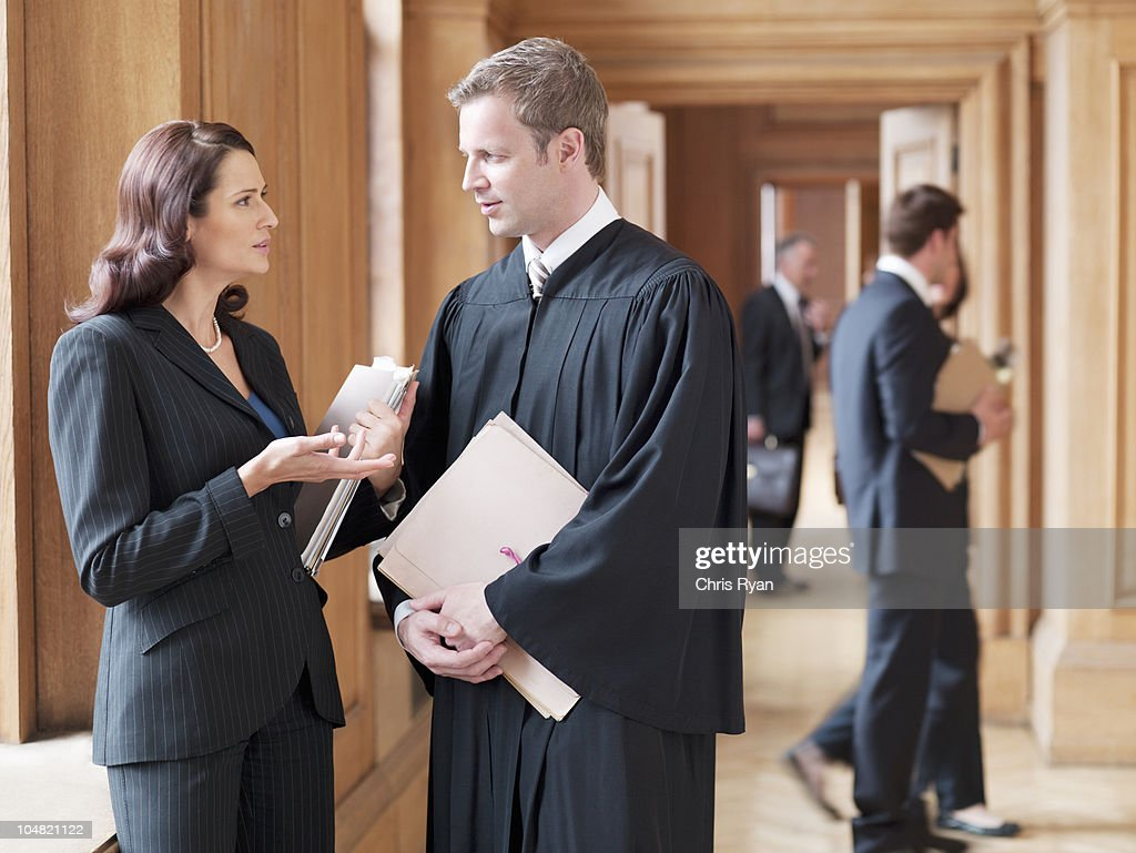 Judge and lawyer talking in corridor : Stock Photo