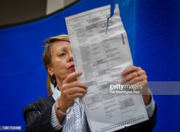 Judge Betsy Benson, Canvassing Board Chair for Broward County Supervisor of Elections Office, shows ballots damaged by machines during the vote...