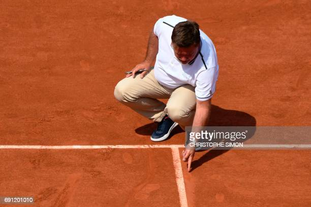 Judge checks a ball print during a tennis match at the Roland Garros 2017 French Open on June 1, 2017 in Paris. / AFP PHOTO / Christophe SIMON
