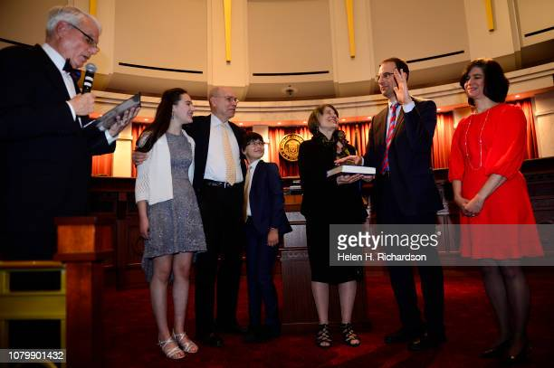 Judge David Ebel left gives the oath of office to newly elected Attorney General Phil Weiser second from right as he raises his left hand during his...