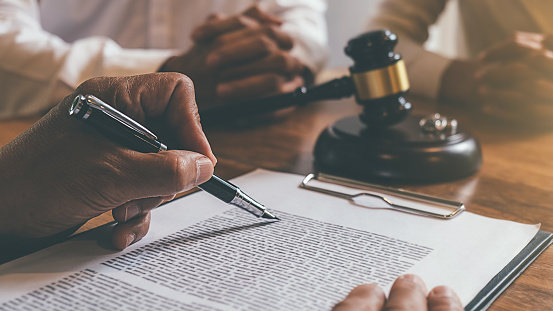 Judge gavel with Justice lawyers deciding, consultation on marriage divorce between married couple and signing divorce documents on table. Concepts of Law and Legal sevices. 1179923359