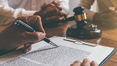 Judge gavel with Justice lawyers deciding, consultation on marriage divorce between married couple and signing divorce documents on table. Concepts of Law and Legal sevices.