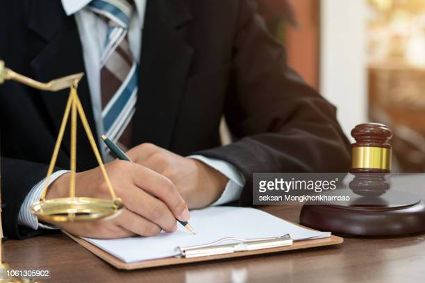 judge gavel with justice lawyers having team meeting at law firm in background. concepts of law. - legislación fotografías e imágenes de stock