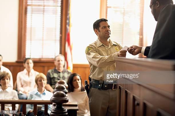 Judge Handing Bailiff a Piece of Paper