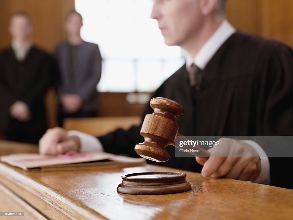 Judge holding gavel in courtroom : Stock Photo