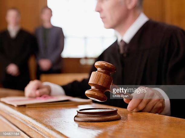 judge holding gavel in courtroom - beslissingen stockfoto's en -beelden
