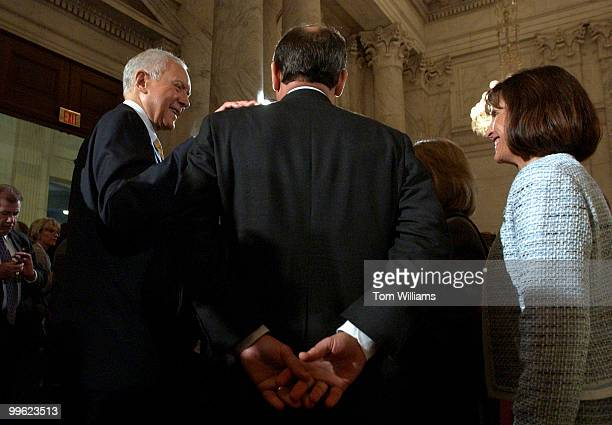 Judge John G Roberts Jr back to camera gets a pat on the back from Sen Orrin Hatch RUtah after the first day of the Senate Judiciary Committee...