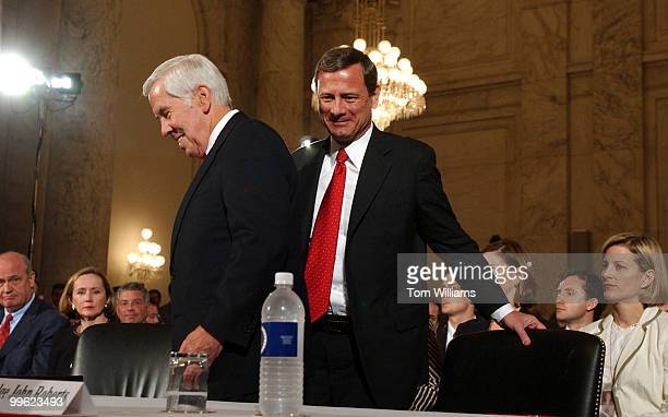 Judge John G Roberts Jr right takes a seat before being introduced by Sen Dick Lugar left on the first day of the Senate Judiciary Committee hearing...