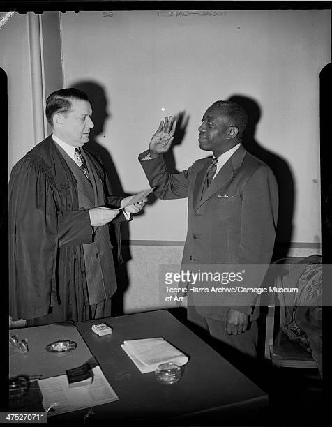 Judge John P Eagan wearing robe swearing in Walter Rainey as County Detective Pittsburgh Pennsylvania March 1946