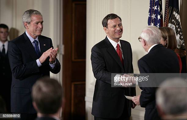 Judge John Roberts, center, shakes hands with Associate Supreme Court Justice John Paul Stevens after being sworn in as the 17th Chief Justice of the...