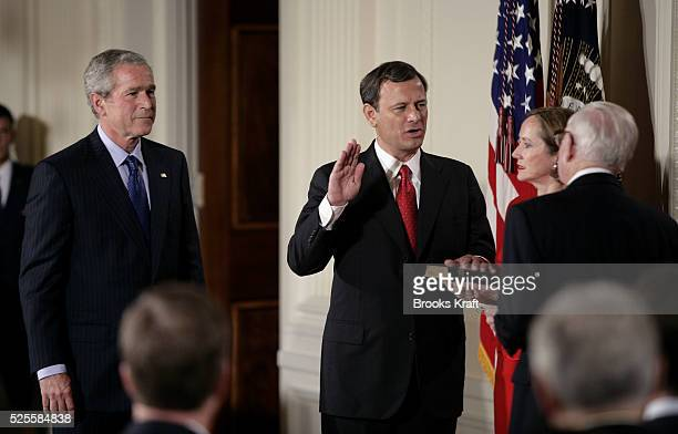 Judge John Robertscenter is sworn in as the 17th Chief Justice of the United States by Associate Supreme Court Justice John Paul Stevens right with...