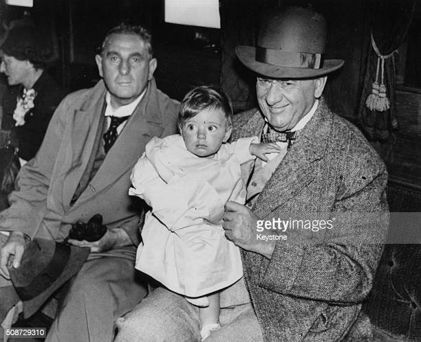 Judge Joseph Franklin Rutherford the head of the Order of Jehovah's Witnesses making friends with a baby passenger while making the voyage from New...